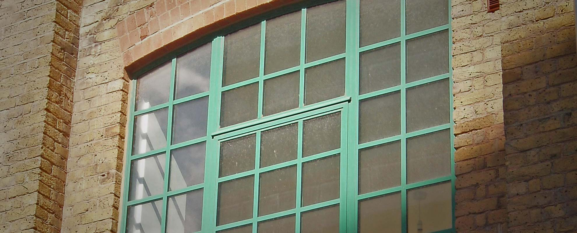 Former chocolate factory in london with new aluminium steel look windows in green